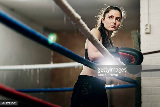 Determined female fighter leaning on ropes