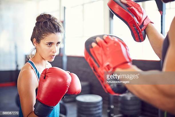 entschlossene boxerin, die im fitnessstudio übt - kampfsport stock-fotos und bilder