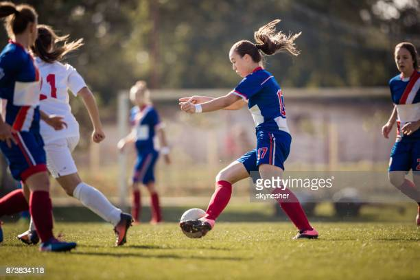 determined female soccer player in action during the match on playing field. - soccer competition stock pictures, royalty-free photos & images