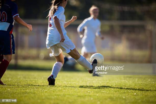 Determined female soccer player kicking the ball on a match.