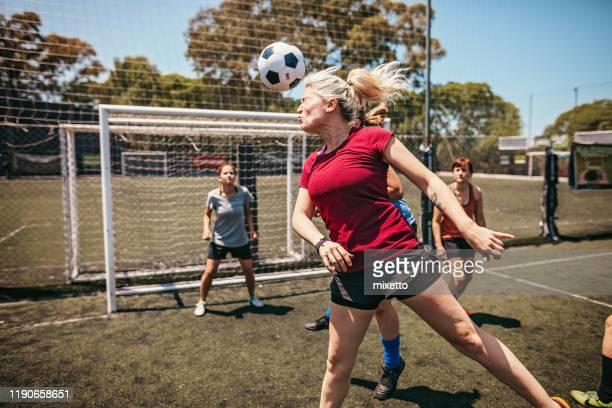decidida jugadora de fútbol femenina jugando con la cabeza durante el partido - fútbol femenino fotografías e imágenes de stock