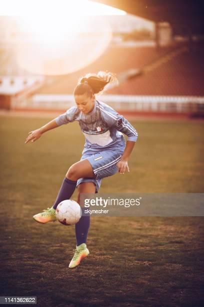 entschlossene weibliche fußballspielerin übt mit ball auf dem feld. - frauenfußball stock-fotos und bilder