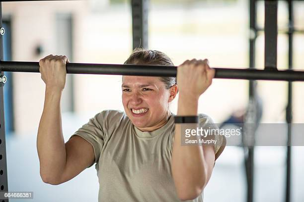 determined female soldier doing pull ups at military air force base - military training stock pictures, royalty-free photos & images