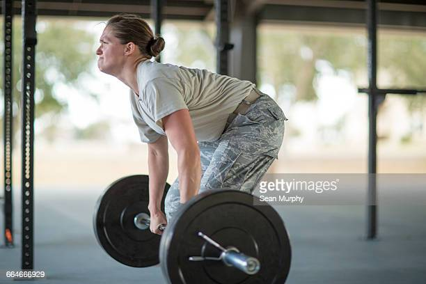 Determined female soldier weight lifting barbell at military air force base