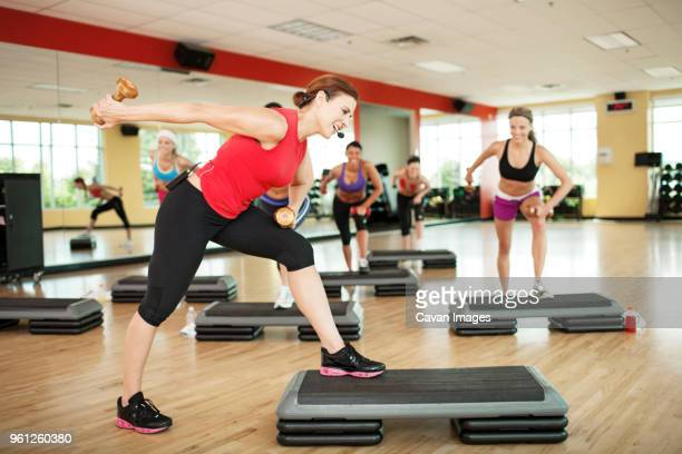 Determined females holding dumbbells while exercising on steps in gym