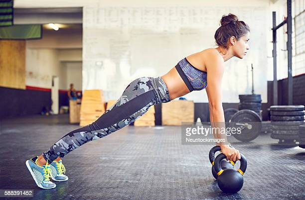 Determined fit athlete doing push-ups on kettlebells in gym