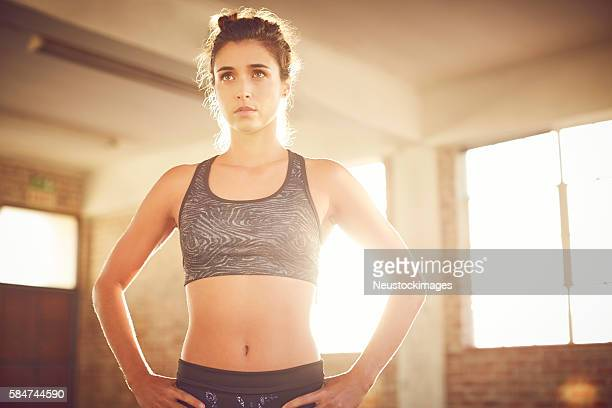 Determined fit young woman with hands on hips in gym