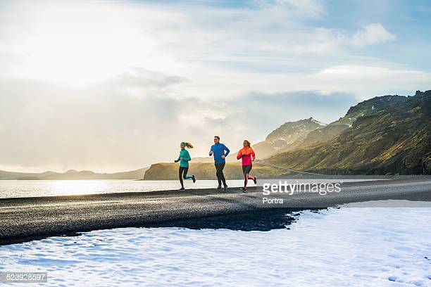 determined friends running on road during winter - mid distance stock pictures, royalty-free photos & images