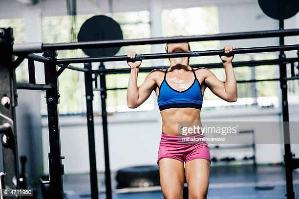Determined girl doing pull-ups
