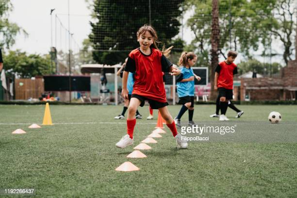 determined girl practicing soccer drills on field - sporting term stock pictures, royalty-free photos & images