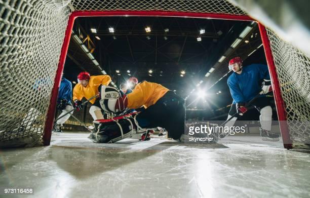 determined goalie defending his goal during an ice hockey game. - difensore hockey su ghiaccio foto e immagini stock