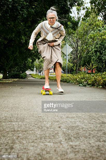 determined grandma on skateboard - young at heart stock pictures, royalty-free photos & images