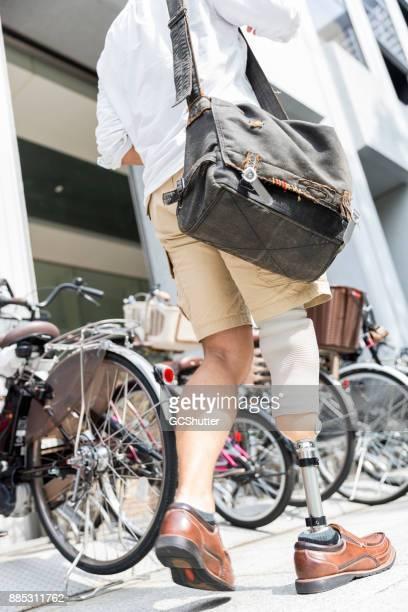 Japanse man dragen prothetische been lopen naar zijn bestemming bepaald