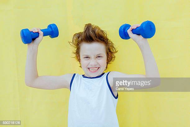 Determined kid lifting weights.