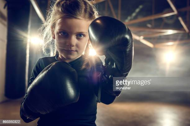 Determined little boxer in a fighting stance on sports training in a gym.