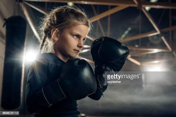 Kleines Mädchen in eine Kampfposition auf Boxtraining bestimmt.