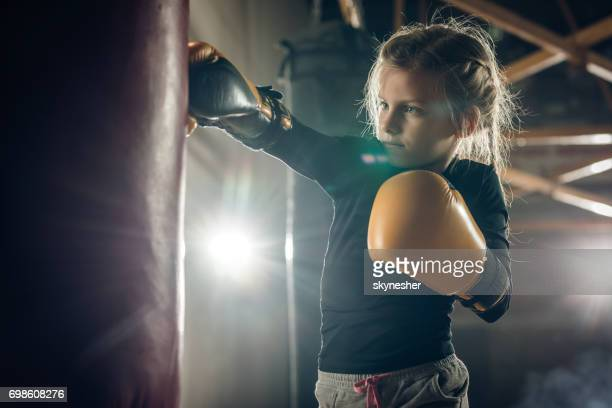 determined little girl punching a bag on a boxing training. - mixed martial arts stock pictures, royalty-free photos & images