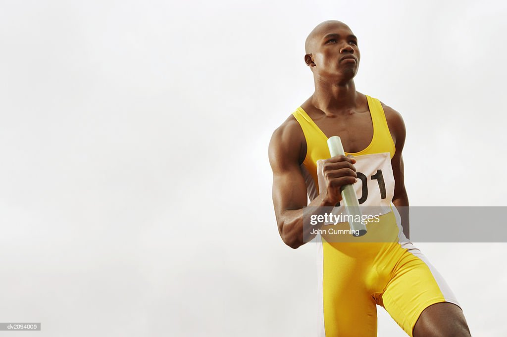Determined Looking Runner Holding a Baton : Stock Photo