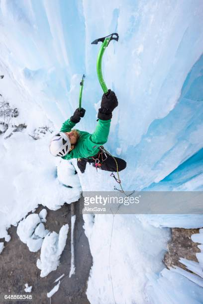 Determined male alpinist ice climbing on frozen waterfall