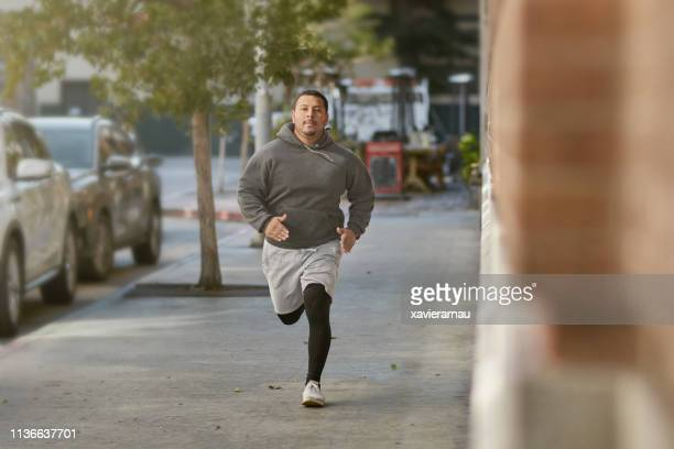 Determined male athlete jogging on sidewalk in city