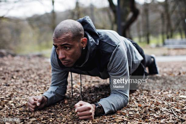 determined male athlete performing plank position in forest - plank exercise stock pictures, royalty-free photos & images