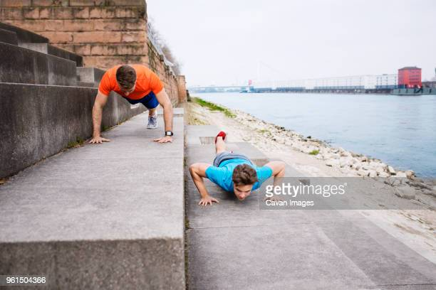 Determined male athletes doing push-ups on steps at beach