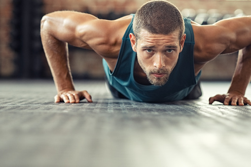 Determined man doing push ups at the gym 1149242526