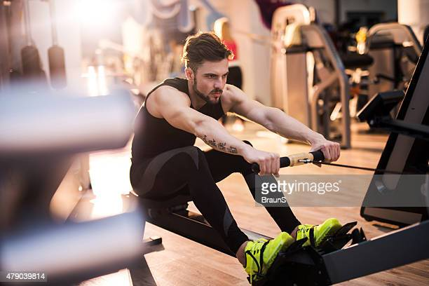 Determined man exercising on rowing machine in a gym.