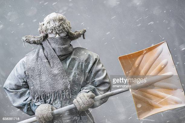 determined man headed out to shovel snow in a blizzard - parka coat stock photos and pictures