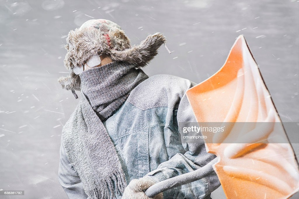 Determined man headed out to shovel snow in a blizzard : Foto de stock