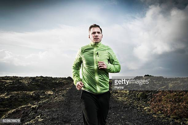 Determined man running on arid landscape