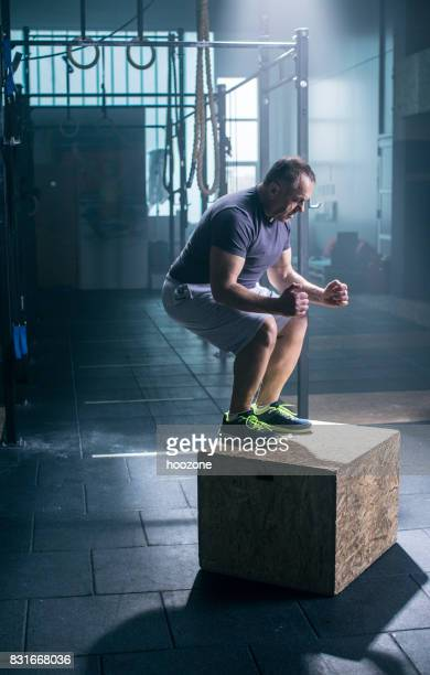 Determined mature man doing box jumping at gym