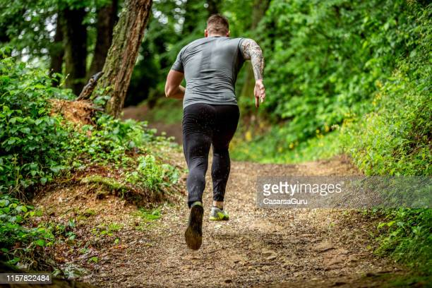determined mid adult jogging in the forest - sprint stock pictures, royalty-free photos & images