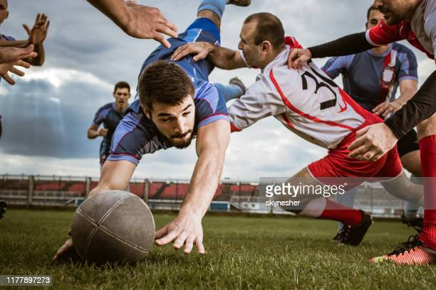 joueur déterminé marquant le touchdown sur un match de rugby au jeu. - touchdown photos et images de collection
