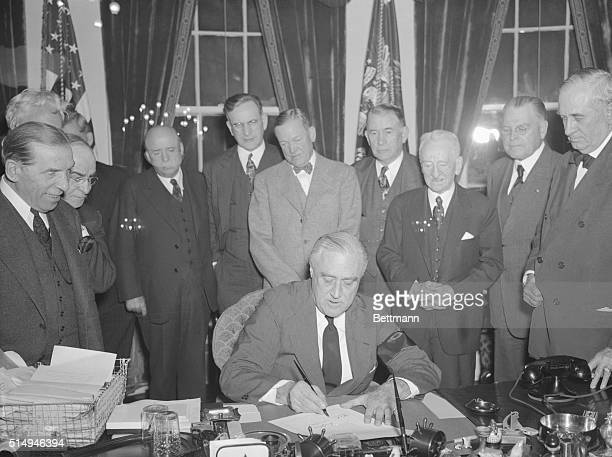 A determined President Franklin D Roosevelt Commander in Chief of the nation's armed forces signs the Resolution declaring that a State of War exists...