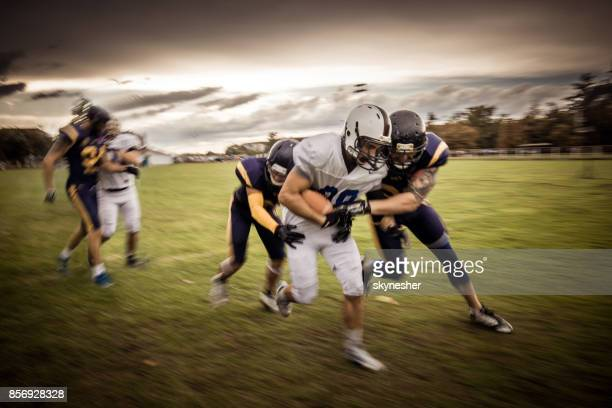 Determined quarterback trying to pass through defensive players on American football match.