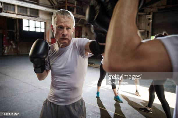 Determined senior male boxer practicing with friend in health club