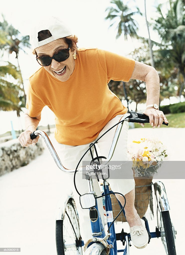 Determined Senior Woman Riding a Bicycle : Stock Photo