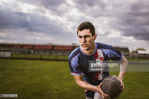 determined sportsman running with ball on rugby field. - rugby union stock pictures, royalty-free photos & images