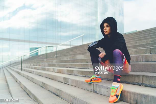 determined sportswoman sitting at the steps - generation z stock pictures, royalty-free photos & images