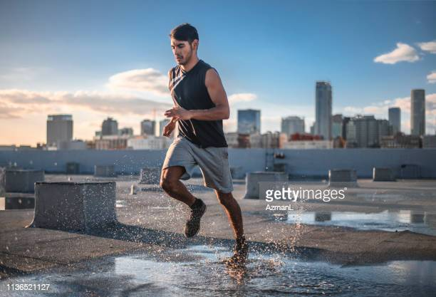 determined sporty young man jogging on terrace - correre foto e immagini stock