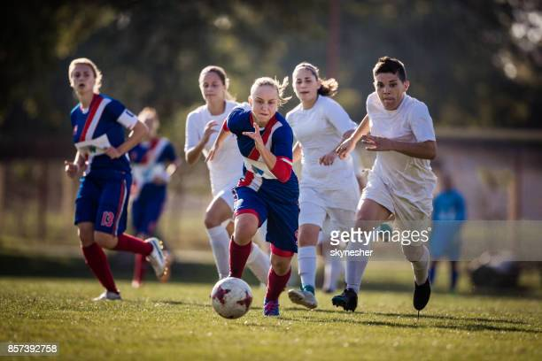 Determined teenage girl running with ball on a soccer match against her opponents.