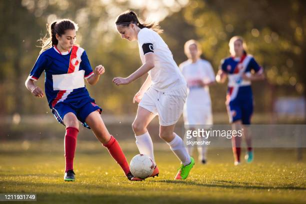 determined teenage girls playing soccer match on a stadium. - soccer competition stock pictures, royalty-free photos & images