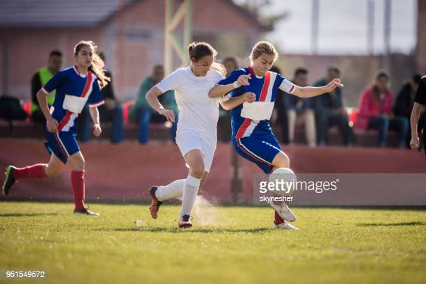 determined teenage girls playing soccer match on a stadium. - tackling stock photos and pictures