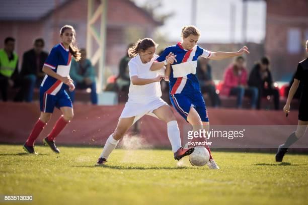teenage-mädchen spielen fußball auf ein sport-spiel im stadion ermittelt. - frauenfußball stock-fotos und bilder