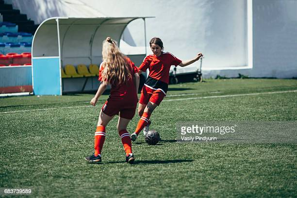 Determined teenagers playing soccer on field