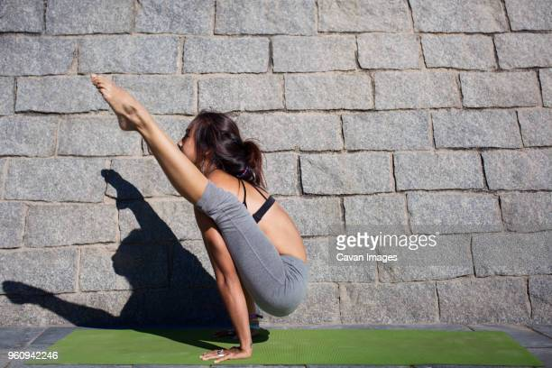 Determined woman doing arm balance yoga pose on sidewalk