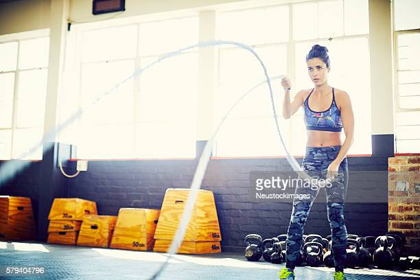 Determined woman doing battling ropes in training gym