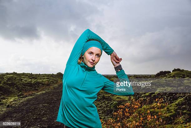 determined woman exercising on arid landscape - long sleeved stock photos and pictures