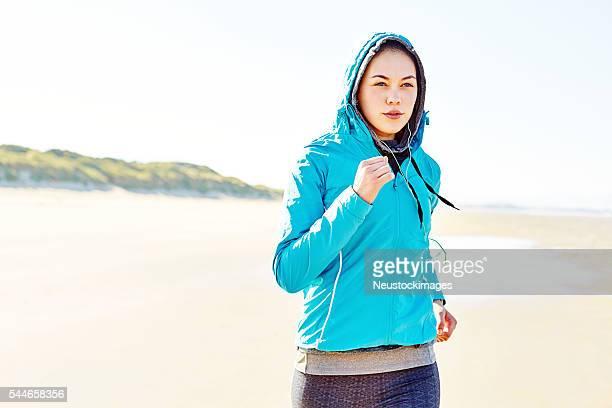 Determinada mulher no casaco com capuz na praia em execução